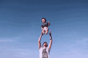 Un homme lance son bébé garçon dans les airs.